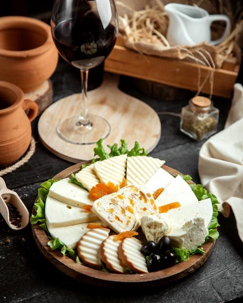 Vista frontal plato de queso con una copa de vino tinto Foto gratis