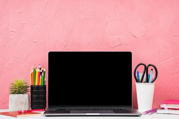 Vista frontal del portátil con elementos de papelería. Foto gratis