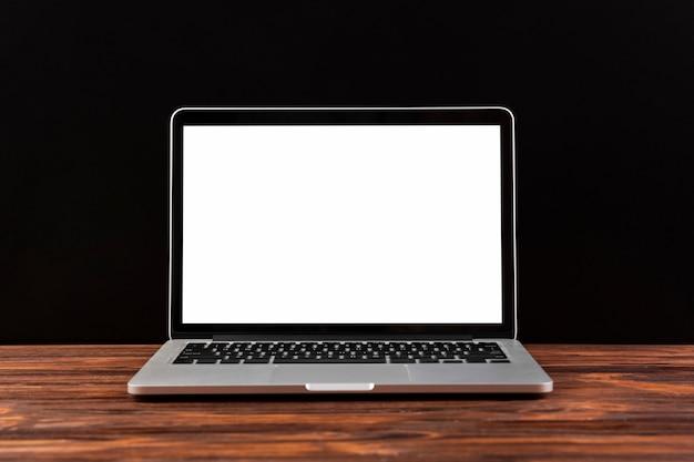 Vista frontal del portátil en la mesa de madera Foto gratis