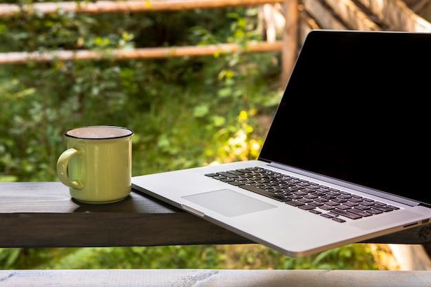 Vista frontal portátil y taza de café Foto gratis