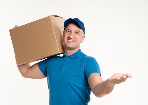 Vista frontal del repartidor llevando una caja de cartón Foto gratis
