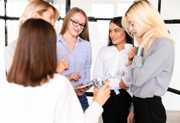 Vista frontal reunión femenina en el trabajo Foto gratis