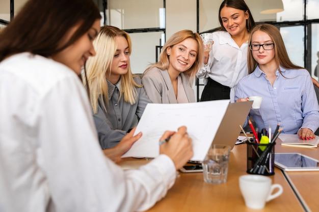 Vista frontal reunión de grupo de mujeres en la oficina Foto gratis
