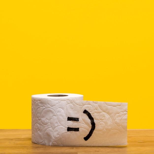 Vista frontal del rollo de papel higiénico con cara sonriente y espacio de copia Foto gratis