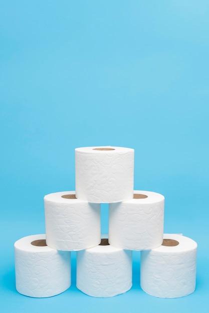 Vista frontal de rollos de papel higiénico apilados en forma de pirámide Foto gratis