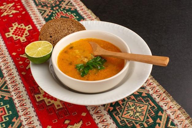Vista frontal sabrosa sopa de verduras dentro de la placa con pan de molde y limón en el escritorio oscuro. Foto gratis