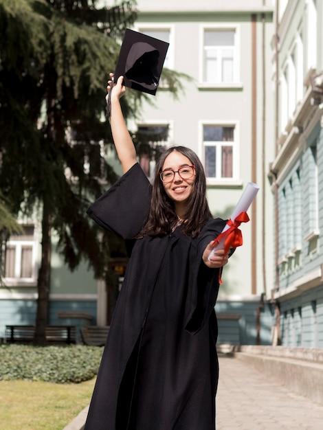 Vista frontal sonriente joven vistiendo toga de graduación Foto gratis