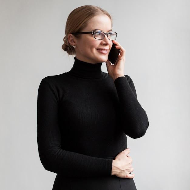 Vista frontal sonriente mujer hablando por teléfono Foto gratis