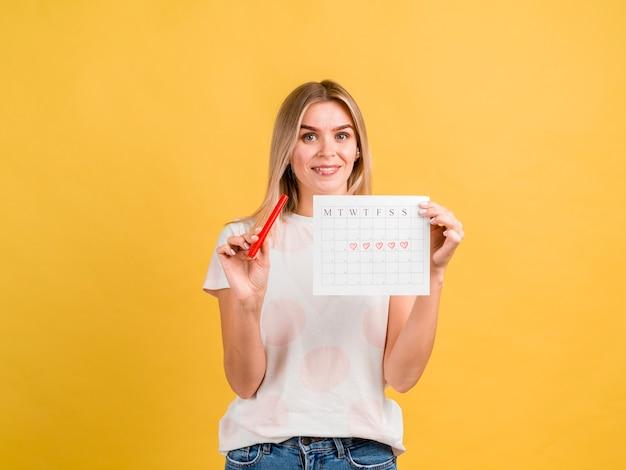 Vista frontal sonriente mujer sosteniendo calendario período Foto gratis