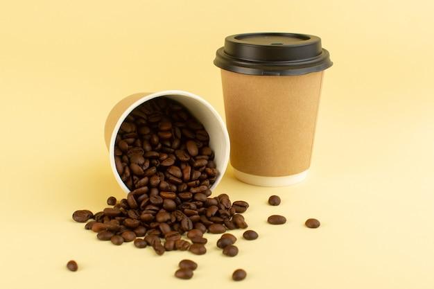 Una vista frontal de tazas de café de plástico con semillas de café marrón sobre la superficie amarilla Foto gratis