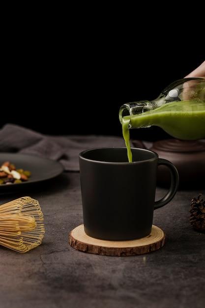 Vista frontal del té matcha vertido en taza Foto gratis
