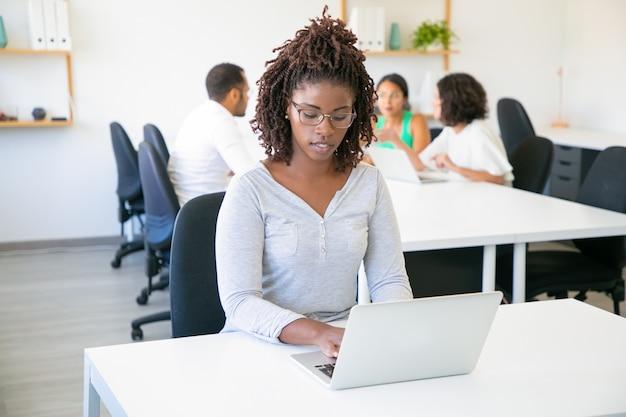 Vista frontal del trabajador atractivo enfocado escribiendo en la computadora portátil Foto gratis