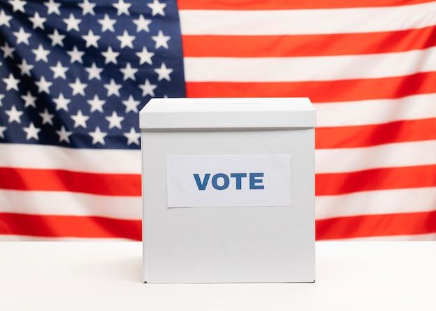 Vista frontal urna blanca y bandera americana Foto gratis