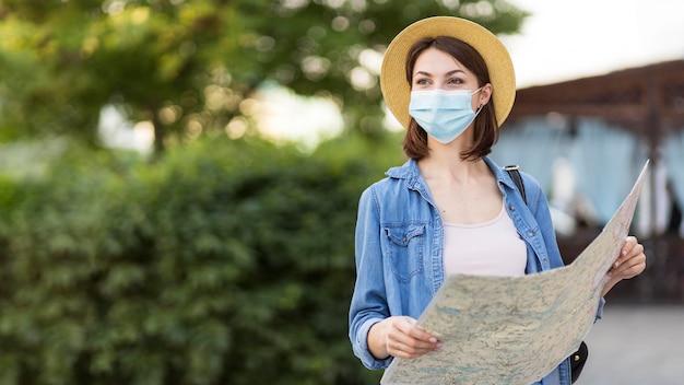 Vista frontal viajero con máscara médica y mapa Foto Premium