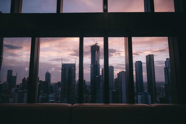 Vista de la hermosa ciudad urbana, altos edificios y rascacielos desde una ventana Foto gratis