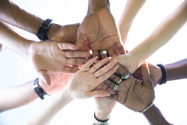 Vista inferior, gente poniendo las manos juntas. Foto gratis