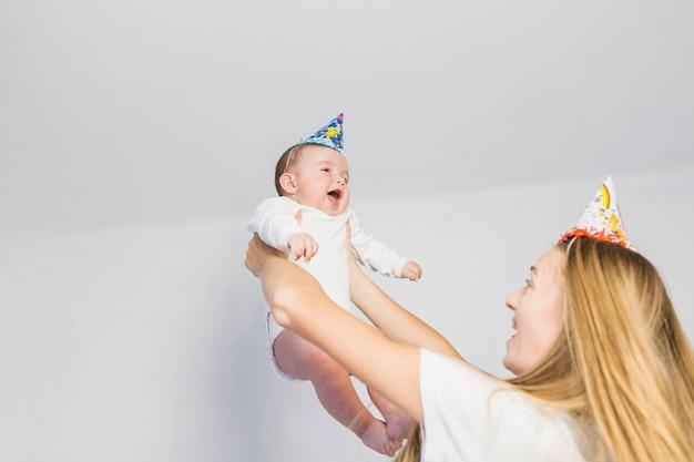 Vista inferior madre jugando con su bebé Foto gratis