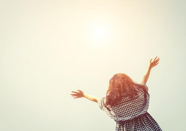 Vista inferior de mujer con los brazos abiertos mirando al cielo Foto gratis