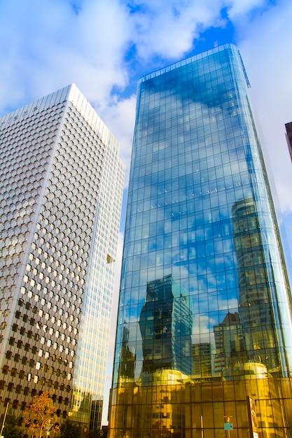 Vista inferior de los rascacielos de cristal del distrito de negocios de parís la defense contra un cielo azul nublado Foto Premium