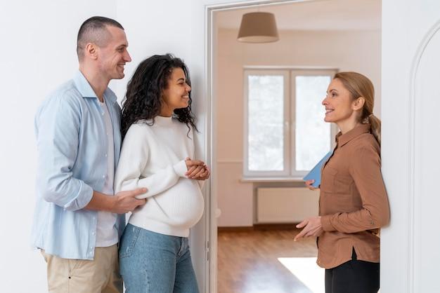 Vista lateral del agente de bienes raíces invitando a la pareja a ver la nueva casa Foto gratis
