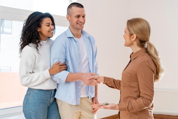 Vista lateral del agente inmobiliario un apretón de manos con la pareja para la nueva casa Foto gratis