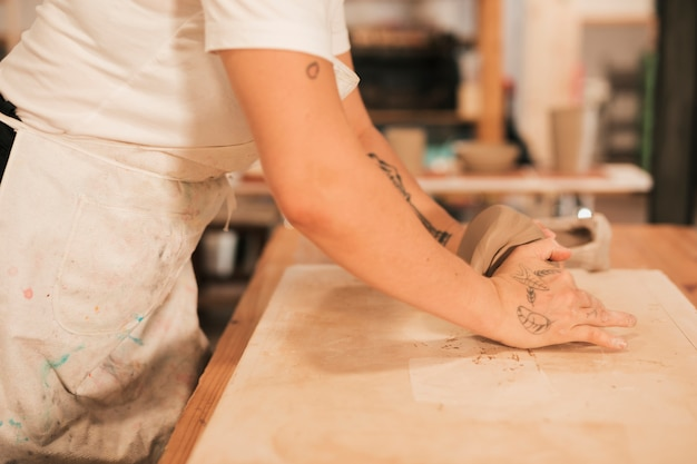 Vista lateral de un alfarero femenino amasando la masa en una mesa de madera Foto gratis