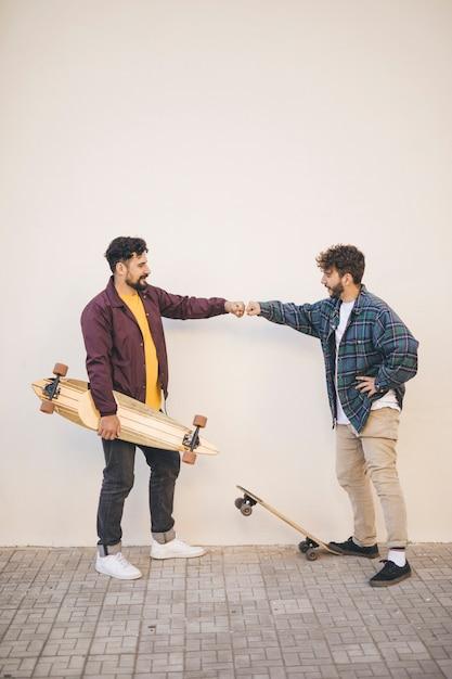 Vista lateral de amigos con patinetas Foto gratis