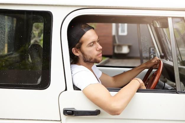 Vista lateral del atractivo joven inconformista barbudo sentado en el asiento del conductor mientras conduce su jeep blanco con el codo colgando de la ventana abierta en un día soleado mientras va a hacer una barbacoa con sus amigos Foto gratis