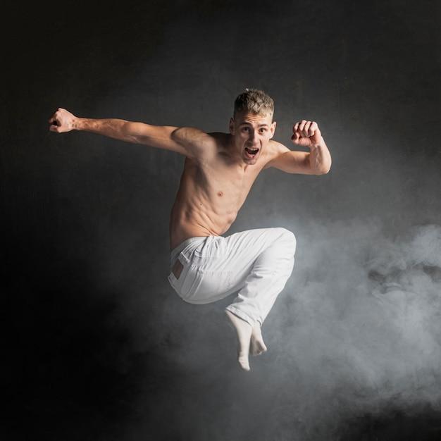 Vista lateral del bailarín sin camisa posando en el aire Foto gratis