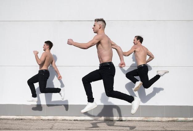 Vista lateral de bailarines de hip hop sin camisa en el aire Foto gratis