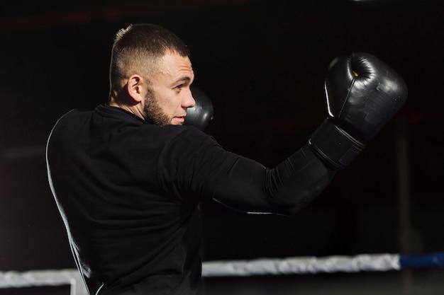Vista lateral del boxeador posando en guantes protectores Foto gratis