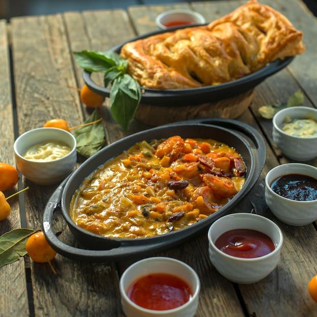 Vista lateral de cazuela con salsas Foto gratis