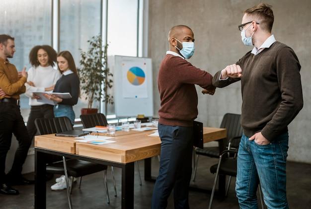 Vista lateral del codo de los hombres saludándose durante una reunión Foto gratis