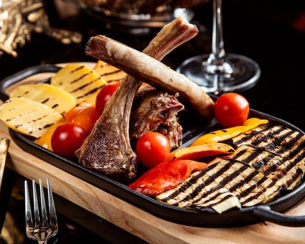 Vista lateral de costillas de cordero fritas adornadas con verduras a la parrilla y tomates frescos sobre la mesa Foto gratis