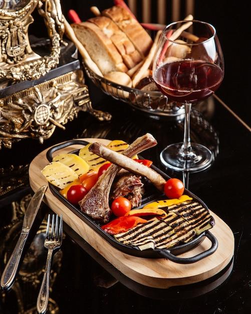 Vista lateral de costillas de cordero frito con papas a la parrilla, tomates frescos y una copa de vino tinto sobre la mesa Foto gratis
