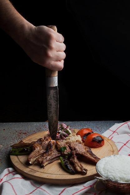 Vista lateral costillas de kebab con verduras fritas y cebolla picada y mano humana y cuchillo y ayran en bandeja de comida de madera Foto gratis