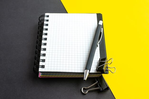 Vista lateral del cuaderno de espiral en el libro y bolígrafos sobre fondo amarillo negro con espacio libre Foto gratis