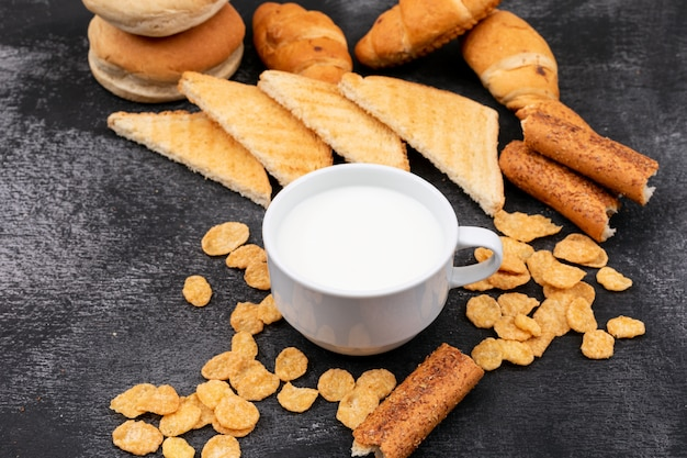Vista lateral de diferentes tipos de pan como galletas, tostadas, cruasanes y leche en superficie negra horizontal Foto gratis