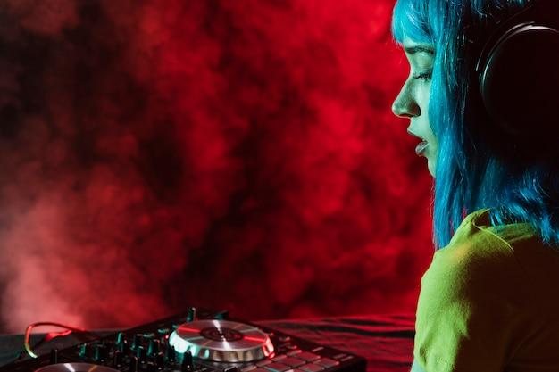 Vista lateral dj femenino mezclado y cubierto de humo rojo Foto gratis