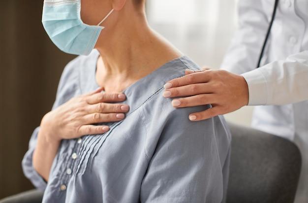 Vista lateral de la doctora del centro de recuperación de covid que controla al paciente anciano Foto gratis