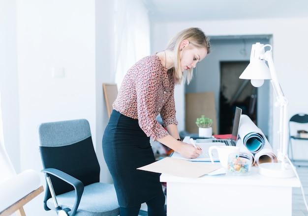 Vista lateral de una empresaria joven que se coloca cerca de la escritura del escritorio en oficina Foto gratis