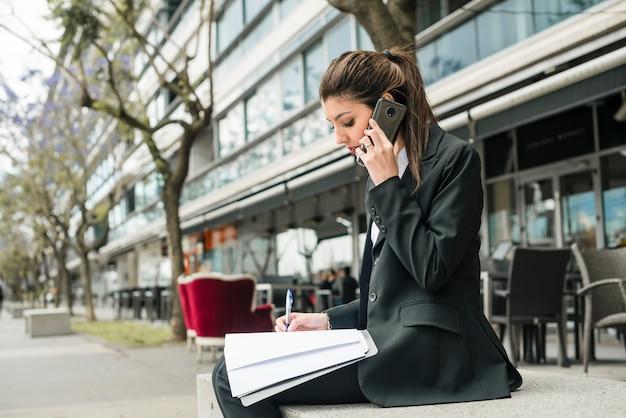Vista lateral de una empresaria joven sentada fuera del edificio escribiendo en la carpeta con la pluma Foto gratis