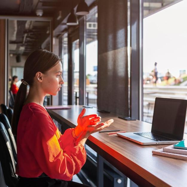 Vista lateral de la empresaria utilizando lenguaje de señas durante la videollamada Foto gratis