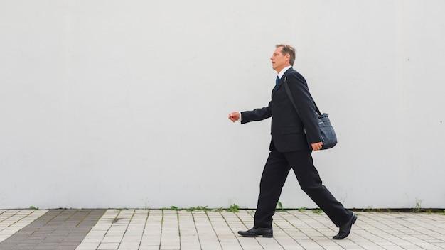 Vista lateral de un empresario maduro caminando sobre el pavimento Foto gratis