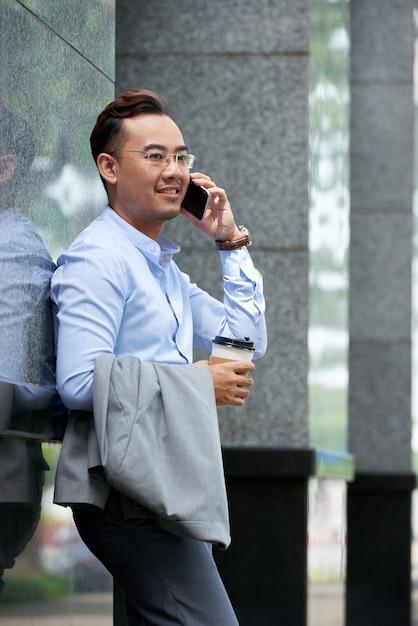 Vista lateral del empresario con teléfono hablar al aire libre en un día de verano Foto gratis