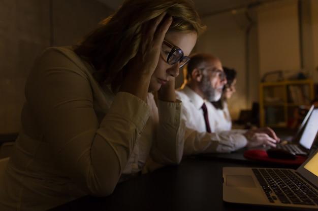Vista lateral de empresarios cansados que trabajan de noche Foto gratis