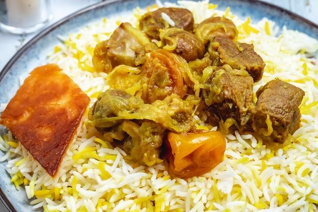 Vista lateral estofado de cordero pilaf agrio con cebolla frita frutos secos castañas y pastel en un plato Foto gratis