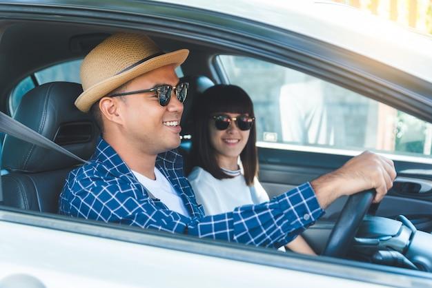 Vista lateral felicidad joven pareja asiática y sonriente sentado en coche. concepto de viaje, primer concepto de seguro de seguridad Foto Premium