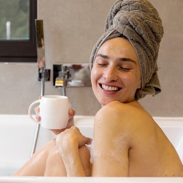 Vista lateral feliz mujer con taza en la bañera Foto gratis