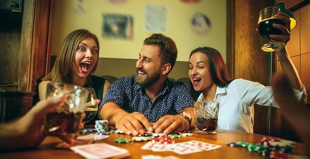 Vista lateral foto de amigos sentados en la mesa de madera. amigos divirtiéndose mientras juegan juegos de mesa. Foto gratis